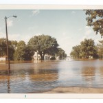 Flood water, Seventh Street Northeast looking north to Crestliner Boats, Little Falls, 1972 Flood, Morrison County, Minnesota. Photo by Sister Karen Rausch. From the Morrison County Historical Society collections, #1977.57.1.p.