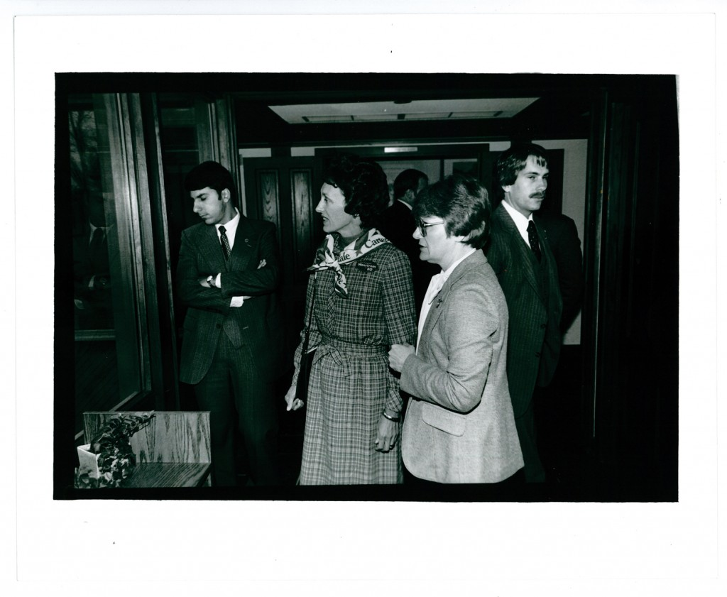 Jan Warner (right) providing a tour of the Weyerhaeuser Museum for Joan Mondale (center), wife of U.S. Vice President Walter Mondale. The men surrounding them are agents of the Secret Service. October 15, 1980. #1981.3.3.