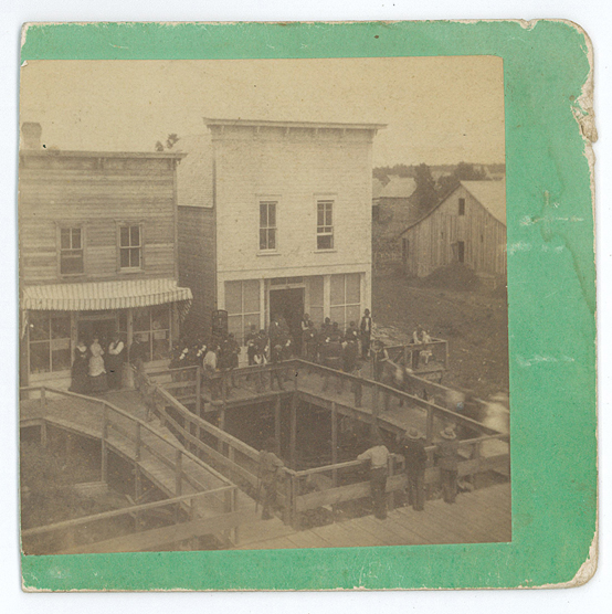 Photo of the Little Falls Ravine at the corner of Broadway and Second Street Northeast, Little Falls, MN. The white building is O. L. Clyde's store. Photo by Neal & Simmons, c. 1883-1885, from the Morrison County Historical Society's collection.