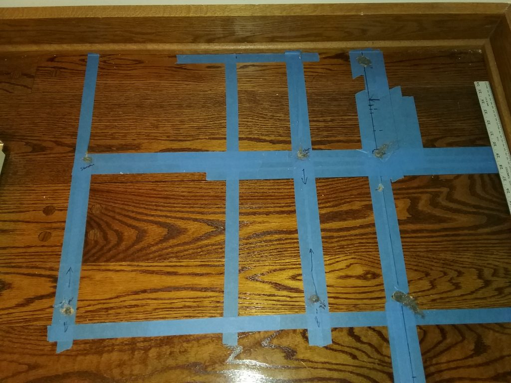 Blue tape grid to help us find sleepers. We drilled 5 holes before striking the first sleeper. The additional 3 holes confirmed the east-west orientation of the sleepers. The Charles A. Weyerhaeuser Memorial Museum, 2019.