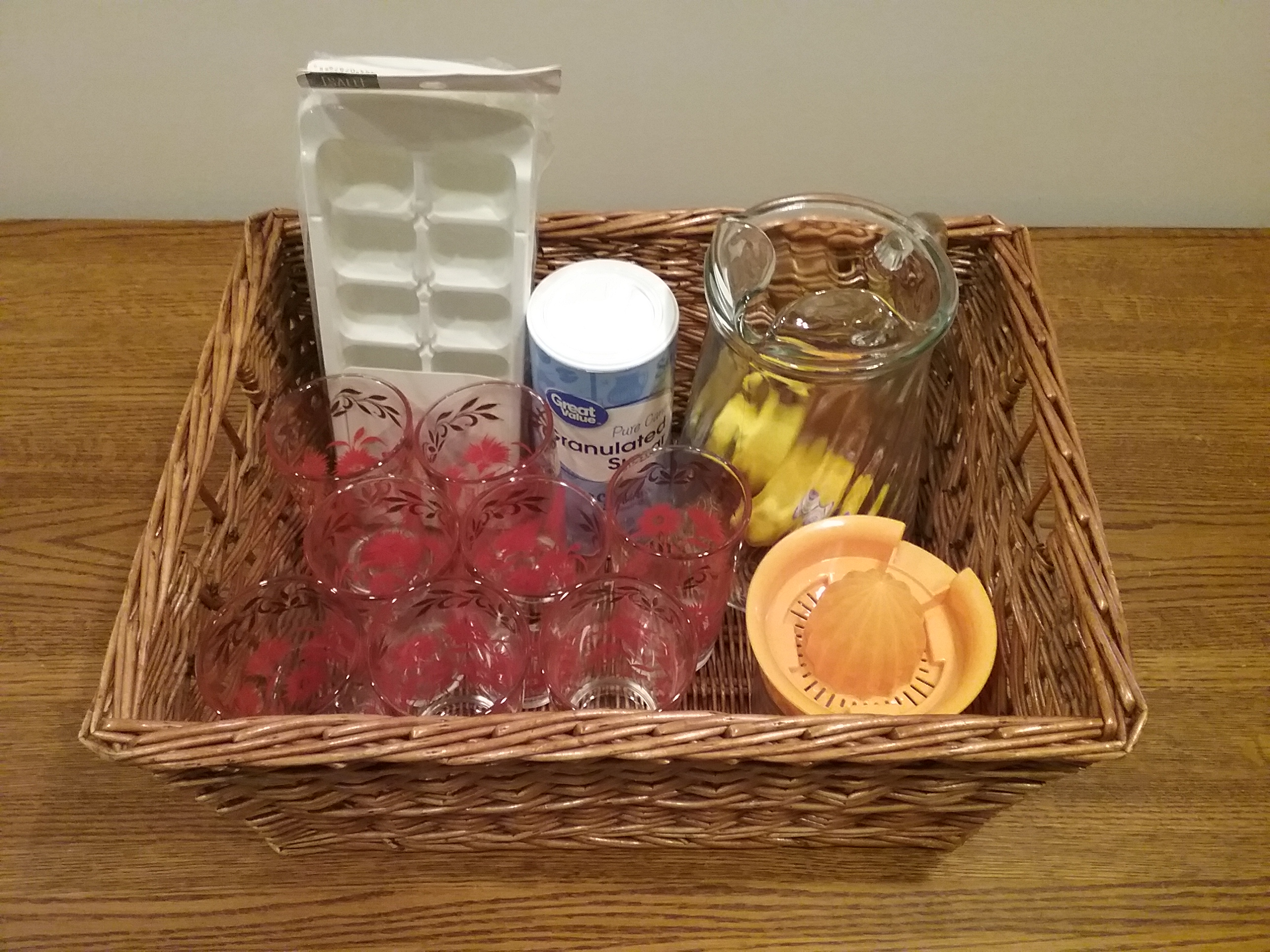 "MCHS Silent Auction Item: Lemonade-making basket including a pitcher and 8 vintage Hazel Atlas ""red carnation"" glasses."