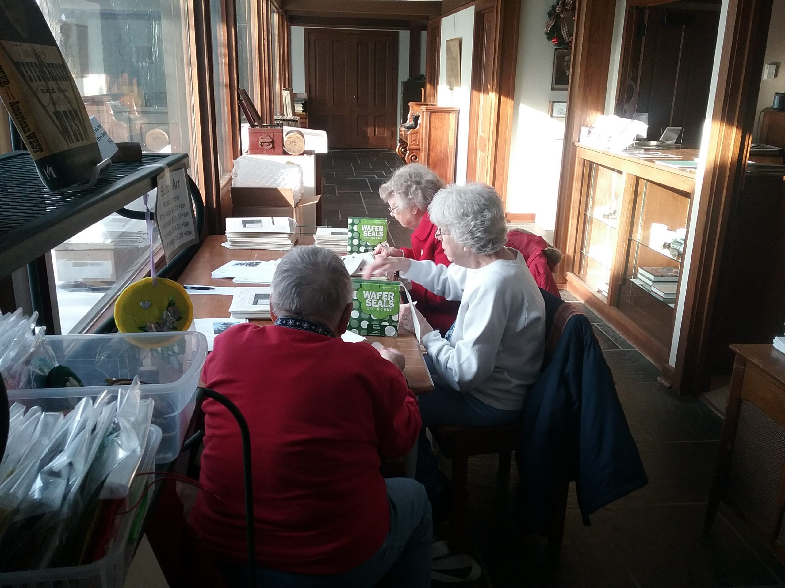 The Weyerhaeuser Museum's A-Team, Alvina, Alice, and Ardyce, folding newsletters, December 21, 2019.