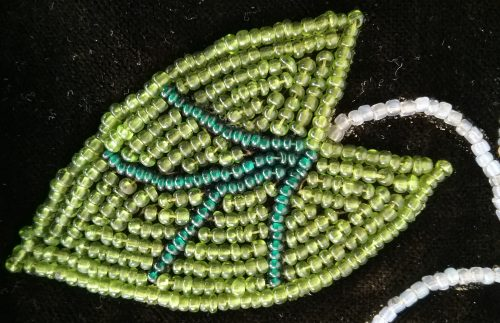 Beaded broad leaf arrowhead from an Ojibwe bandolier bag in the Weyerhaeuser Museum's collection.