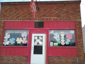 Colorful paper hearts in the windows of the West Side Cafe, West Broadway, Little Falls, MN, April 15, 2020.