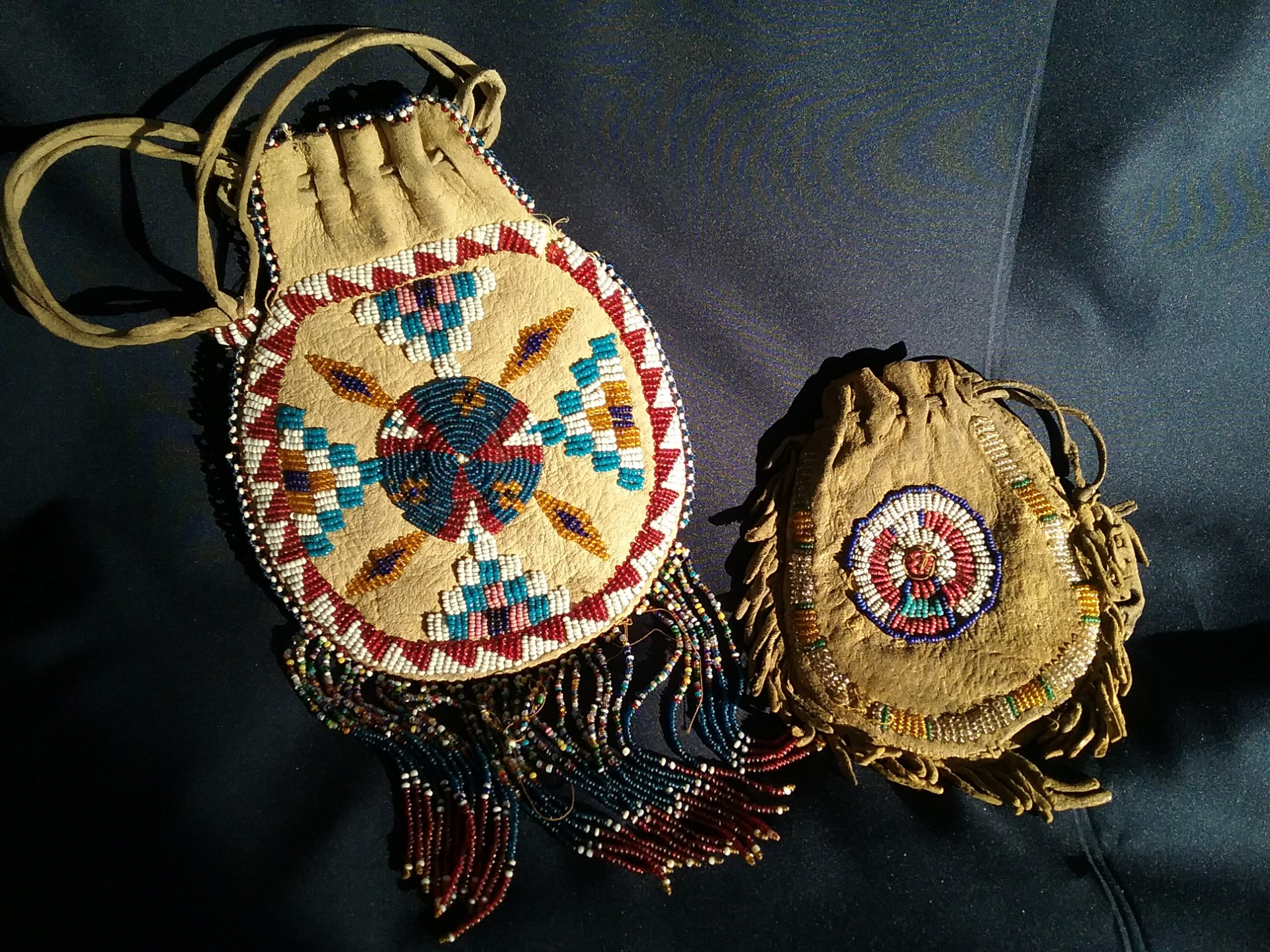 Two Native American leather bags featuring seed bead designs. The bag on the left is from a Native tribe of unknown origin. The bag on the right is from the Blackfoot Nation. MCHS collections, #1984.14.1 and 1990.28.1.