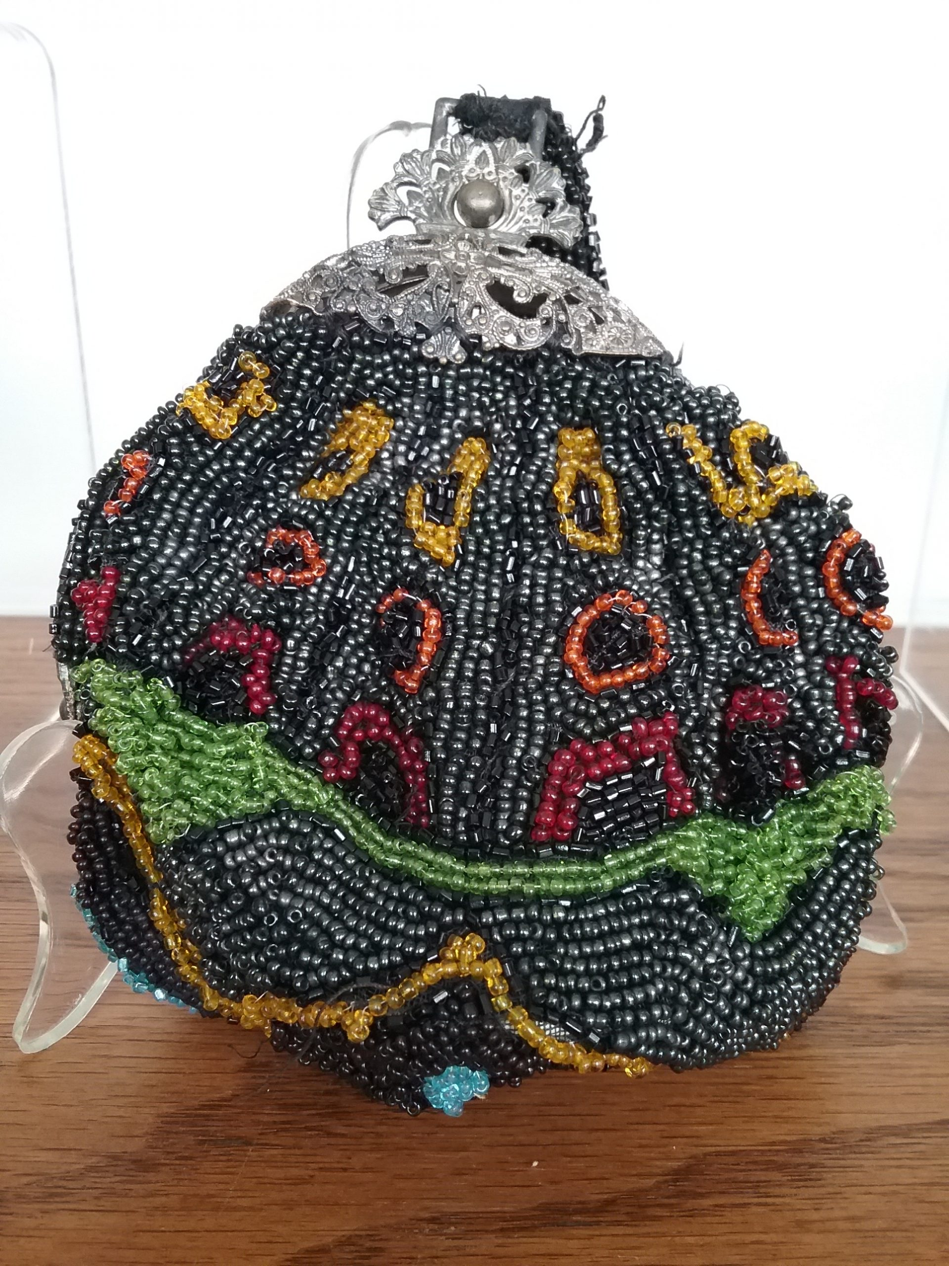 Evening Handbag: Victorian-era evening handbag beaded in black, red, orange, yellow, and green seed beads. There is a mirror on the inside in the bottom of this handbag. Unknown donor. MCHS collections, no accession number.