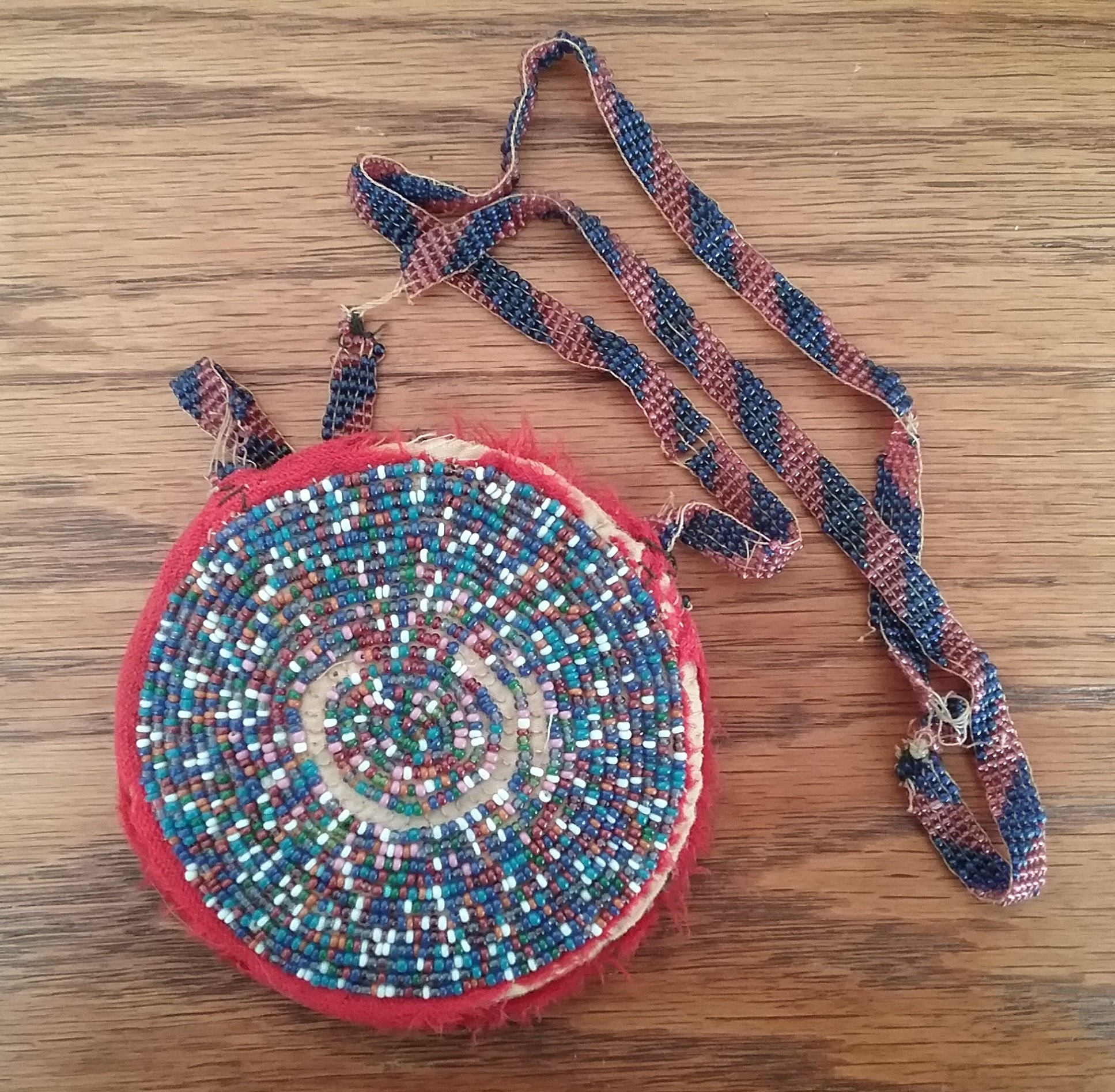 Coin Purse: Round beaded coin purse with beaded strap (second side featuring multi-colored seed beads in random pattern), donated by Viola & Frances Landmeier in 1970. MCHS collections, #1970.22.14.