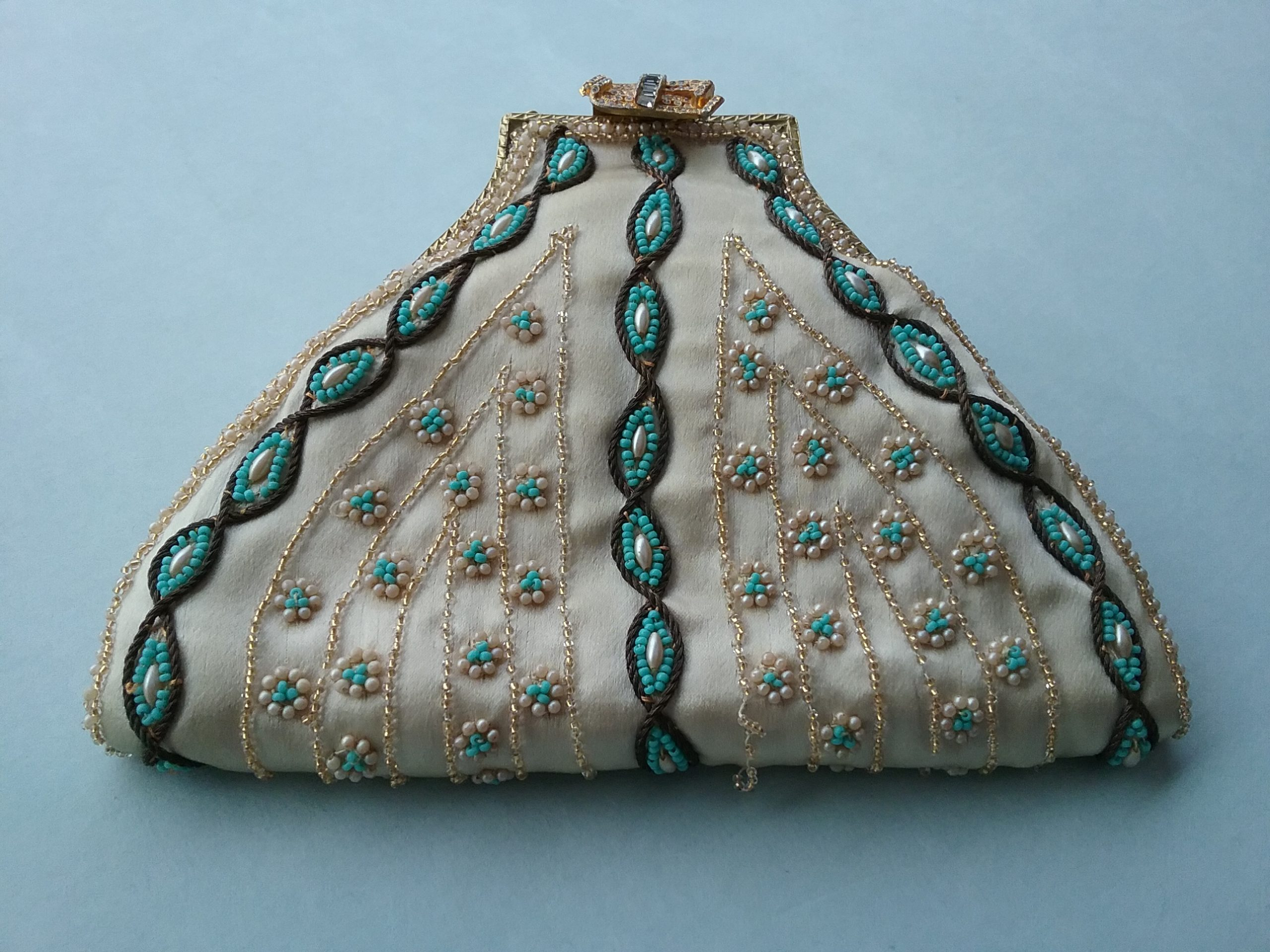 Clutch Purse: Cream-colored satin clutch purse with turquoise, gold, and imitation pearl beads. Donated by Mrs. Vernon Johnson. MCHS collections, #1973.20.1a.