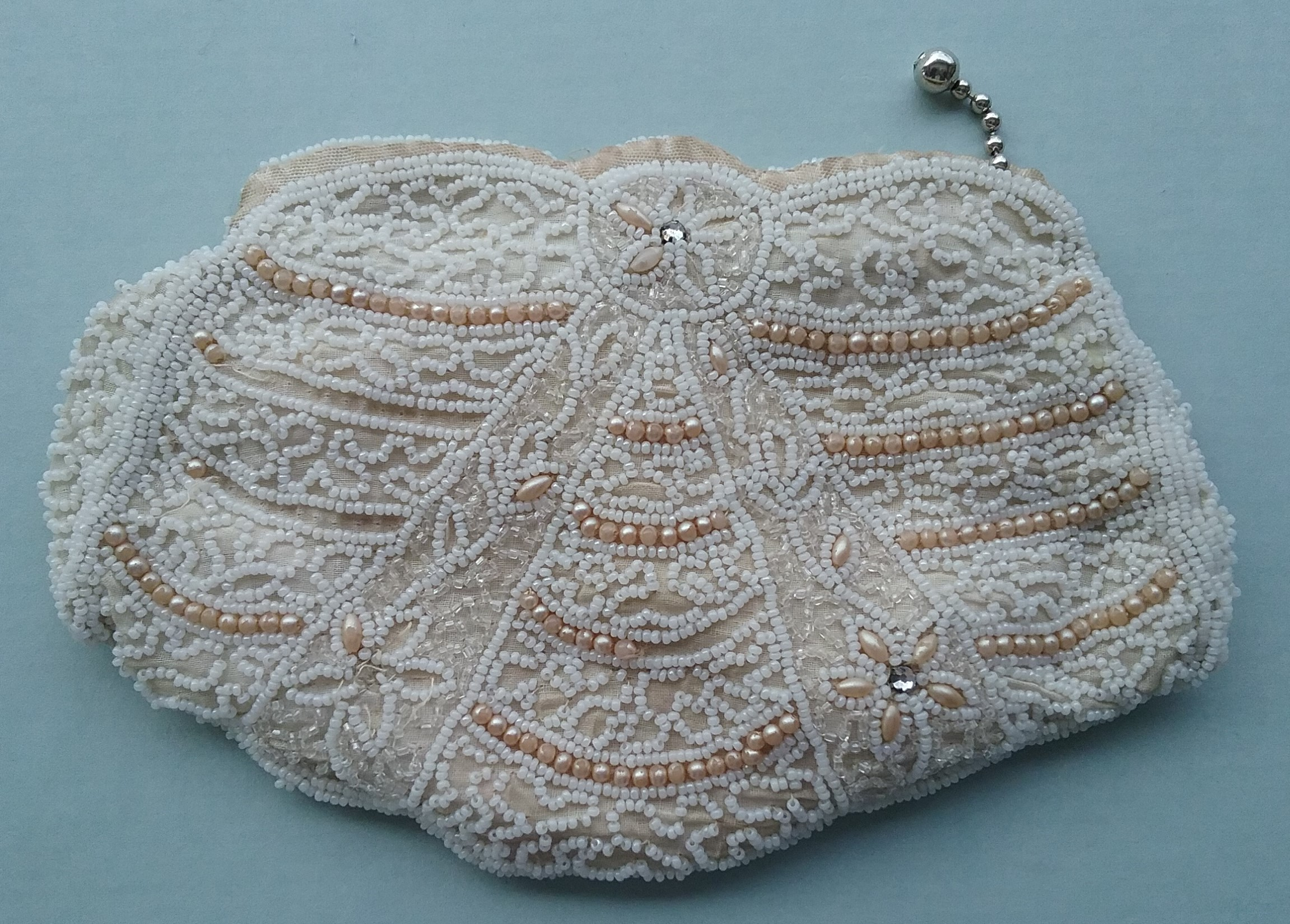 Clutch Purse: White clutch purse with clear and white seed beads, imitation pearl beads, and 2 rhinestones. Donated by Lucy Tanner. MCHS collections, #1993.46.32.