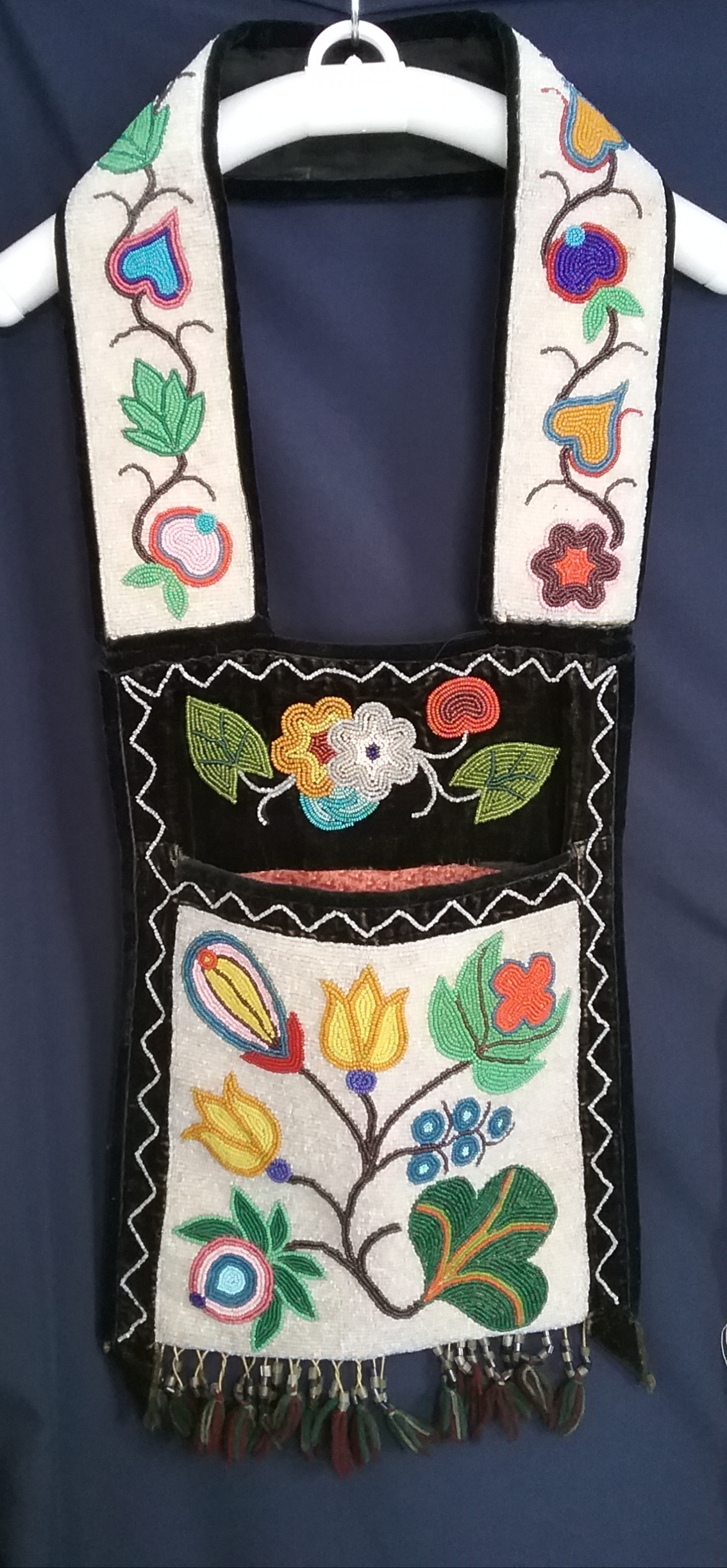 Small Ojibwe Gashkibidaagan: This Ojibwe gashkibidaagan (bandolier bag) was purchased by Upsala resident Jean Martinson at a garage sale in Mispah, Minnesota. She paid a quarter for it. The bag was originally taken as payment for a grocery store bill in the Turtle Mountains of North Dakota. Jean owned the bag for 20 years before donating it to the museum in 1996. The beadwork is spot-stitch applique. Note the floral motif and that the pattern from one side of the strap to the other is not identical. Based on the design, this bag was likely produced by someone in the White Earth Band. MCHS collections, #1996.36.3.