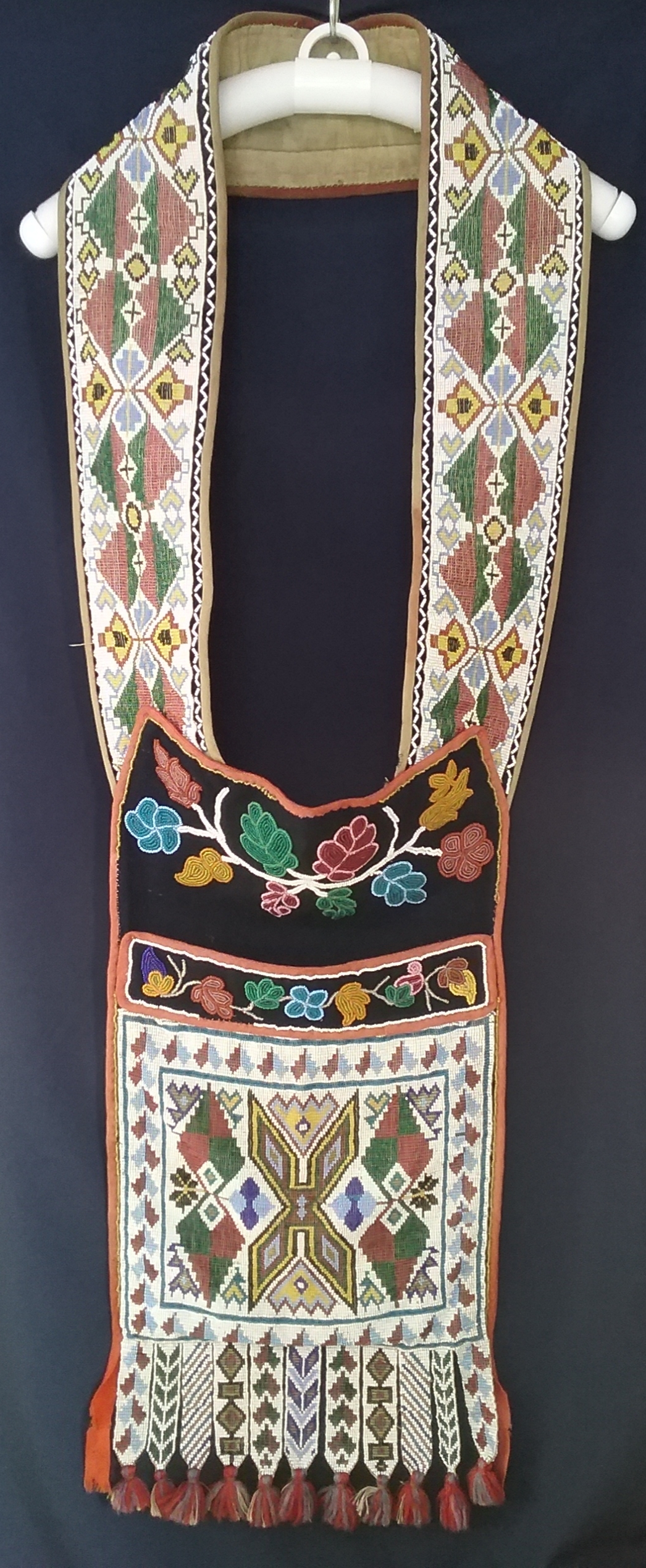 Ojibwe Gashkibidaagan Owned by Nathan Richardson: This Ojibwe gashkibidaagan (bandolier bag) was presented by Mille Lacs Band Chief She-bosh-king to Nathan Richardson (called the Father of Morrison County) in 1884 for his work in assisting the Band with legal matters. The front panel, strap, and fringe feature loom-woven beading, while the sections at the top of the pocket and above the pocket are done in spot-stitch applique. Note the symmetry within the beadwork on the strap and the large X in the center of the pocket. The X was a common motif for Ojibwe loom-woven gashkibidaaganag. MCHS collections, #1940.42.1.