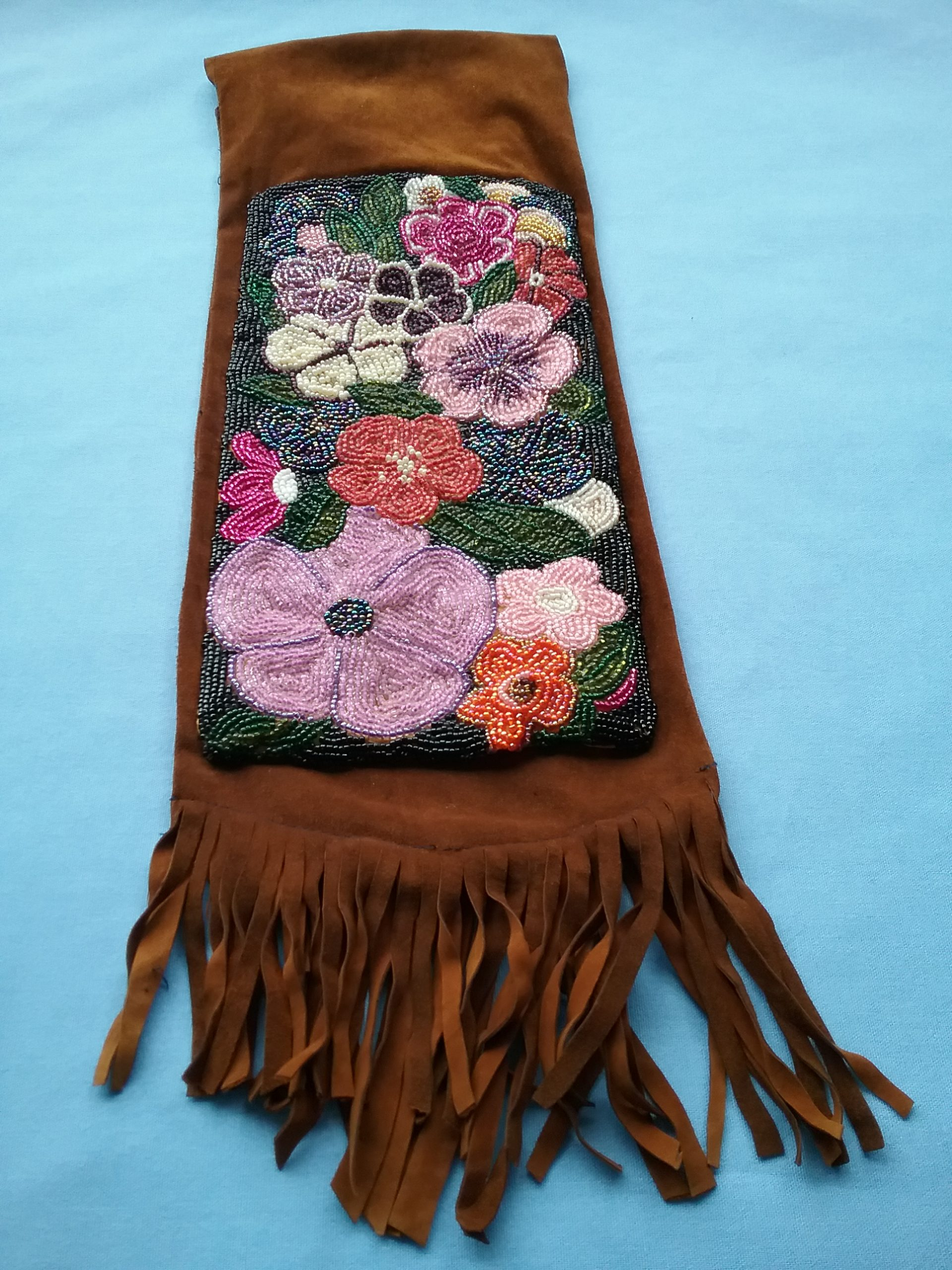 Beaded leather bag made by Sister Carol Schmit, OSF. Sr. Carol was inspired by Ojibwe floral motifs in creating this bag, which was made to hold precious elements like stones and sweet grass. The dark colors in the design are meant to indicate the many beauties of nature that are being lost. On loan for the BEAD Exhibit from Sr. Carol Schmit.