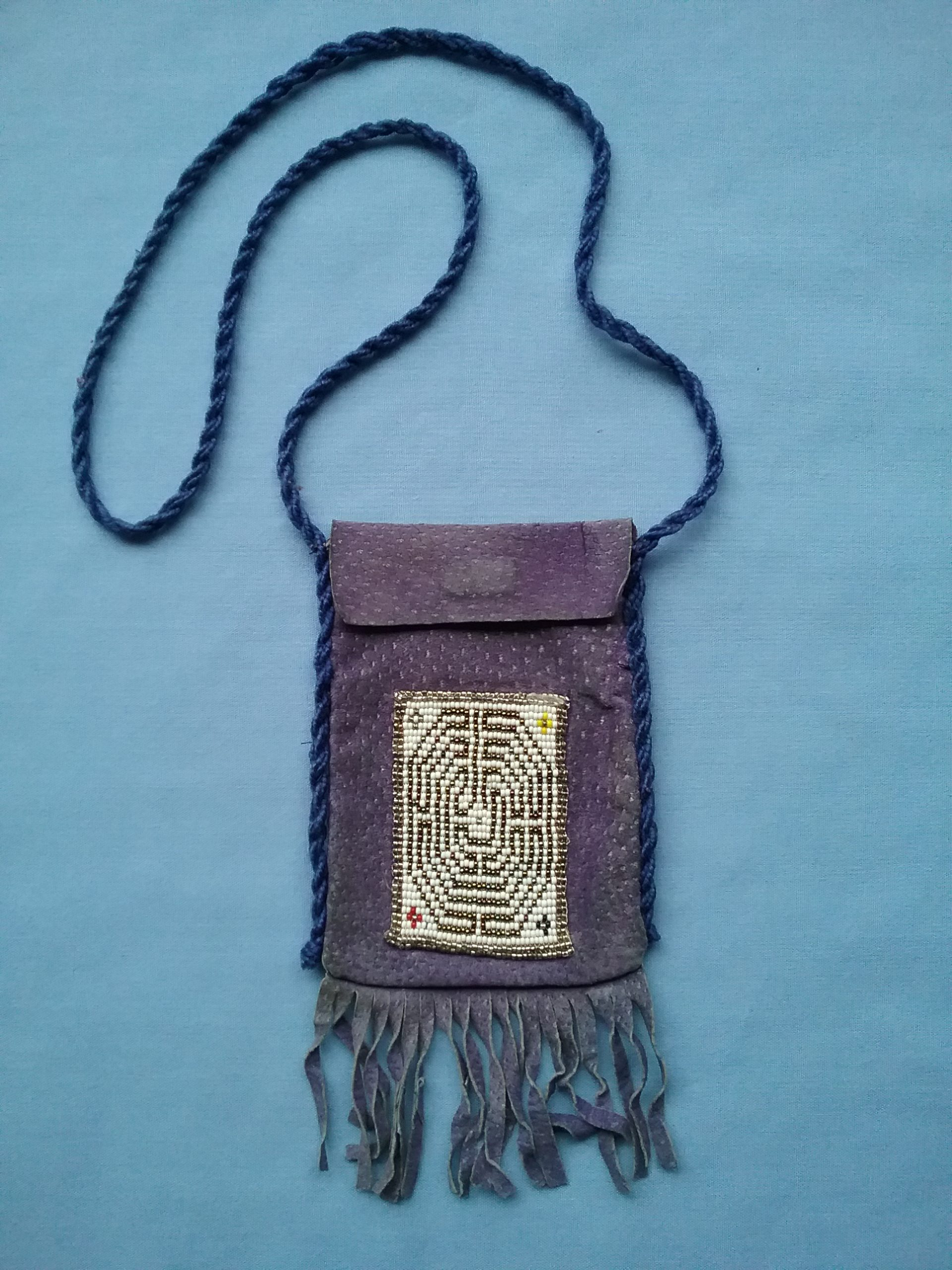 """Beaded bag with long cord for wearing around the neck. Made in the 1990s by Sister Carol Schmit, OSF, who uses this bag to carry her cell phone. The beaded labyrinth design was made on a loom and is patterned on the """"Baby Chartres,"""" a shortened rendition of the famous design in the floor of the Cathedral in Chartres, France. The tiny crosses in the corners are of yellow, red, black, and white, indicating the four directions. On loan for the BEAD Exhibit by Sister Carol Schmit."""