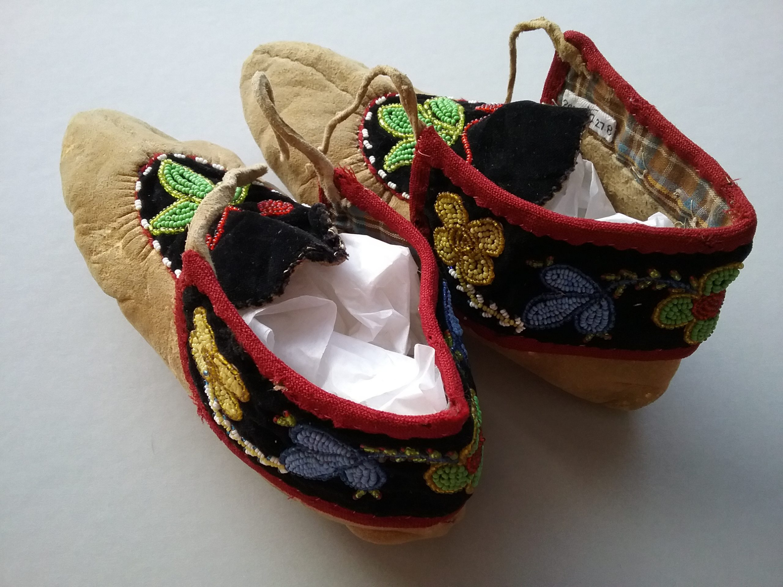 Ojibwe leather moccasins featuring spot-stitch applique beading. Artist unknown. Donated by Katie Jongewaard. MCHS collections, #2005.97.27a&b