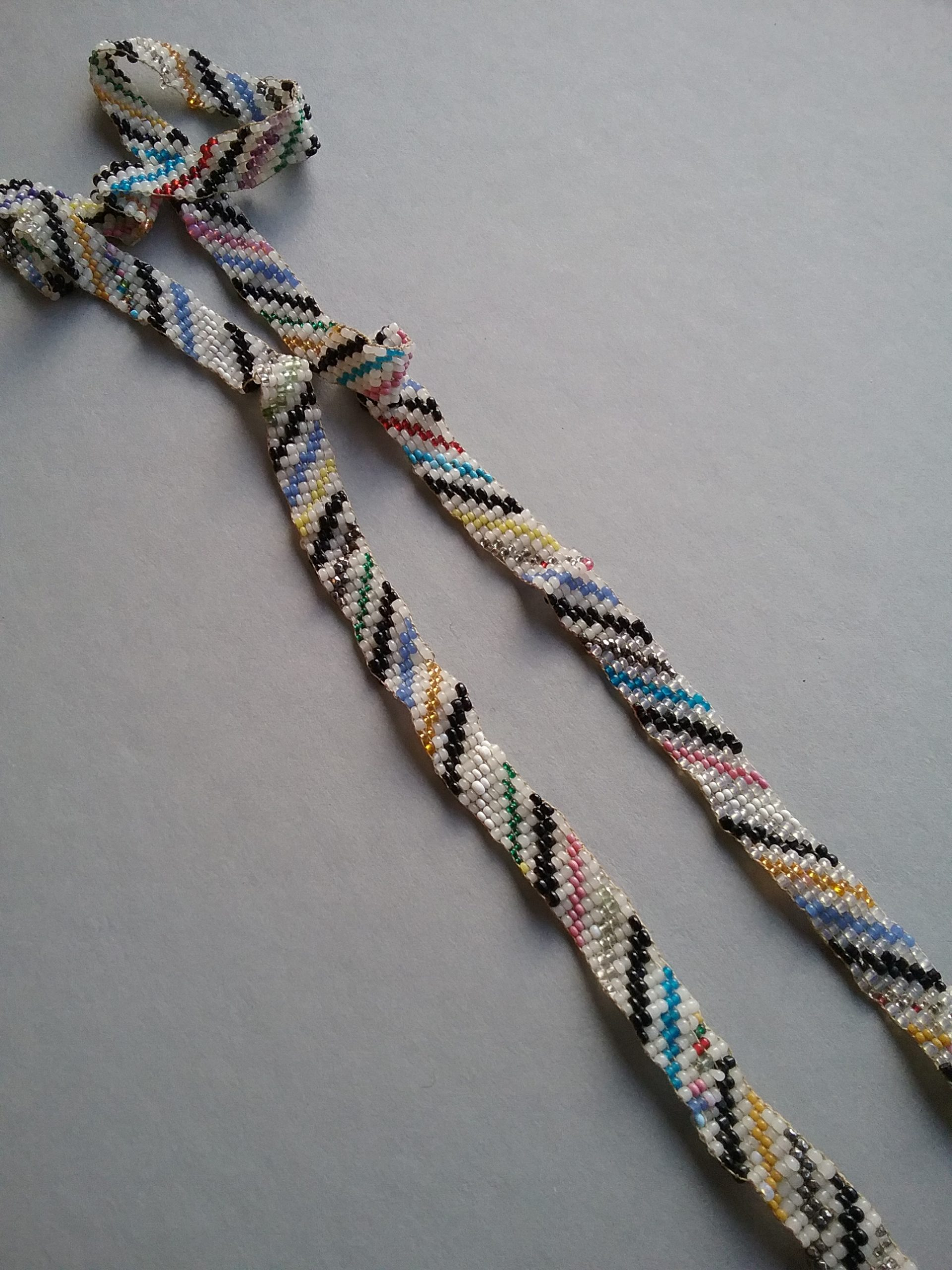 Narrow loom-woven band of beads with a striped pattern from the Hill & Richardson store operated in the 1870s by E.G. Hill and Nathan Richardson. Likely of Ojibwe origin. MCHS collections, #1945.76.