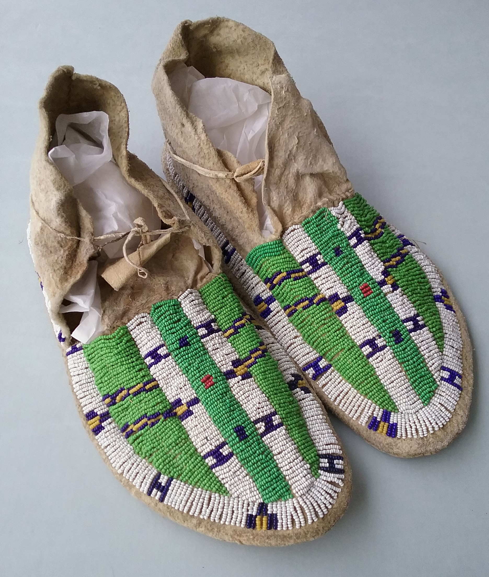 Native Moccasins: This pair of Native moccasins came to the Morrison County Historical Society in 1945. They are leather and feature seed beads spot-stitch appliqued into geometric patterns. Tribal affiliation and artist unknown. Donated by Mike Schomer. MCHS collections, #1945.4.