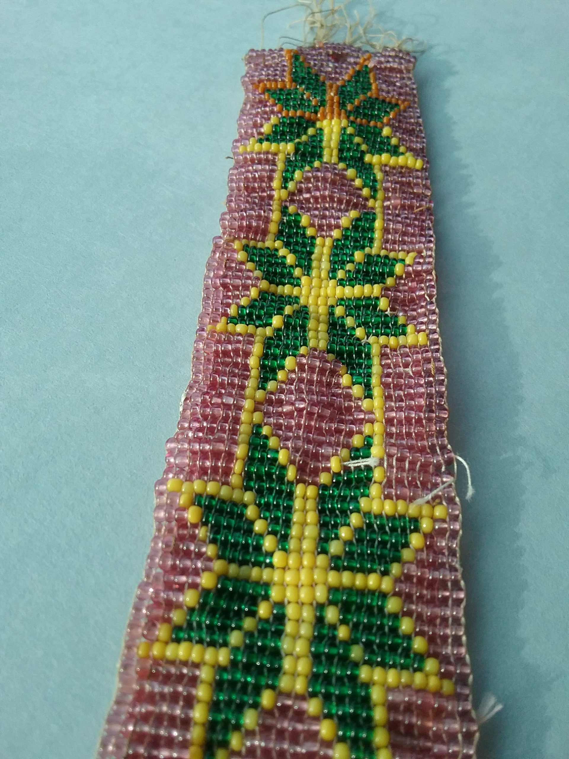 Closeup of beaded band: Loom-woven beaded band with pink, green, and yellow seed beads. Note that the artist switched to orange beads rather than yellow at the very end. MCHS collections, #1945.76.9.