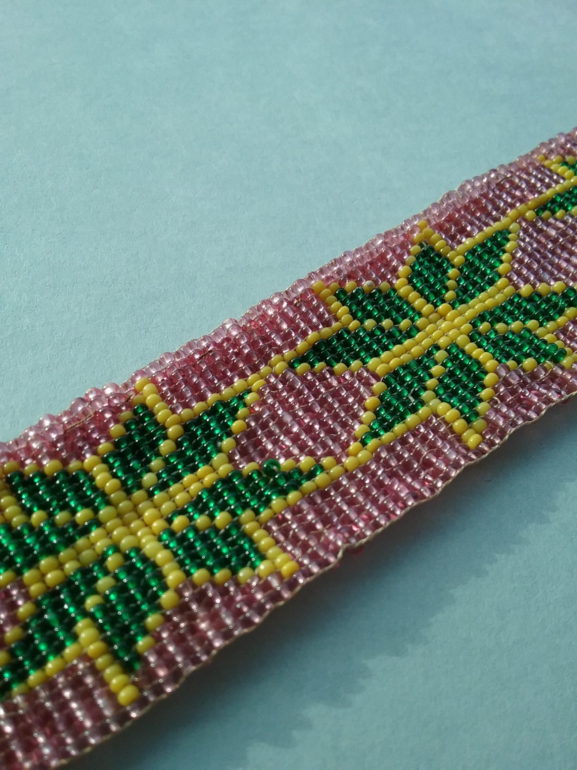 Detail of beaded band: Loom-woven beaded band with pink, green, and yellow seed beads. MCHS collections, #1945.76.9.