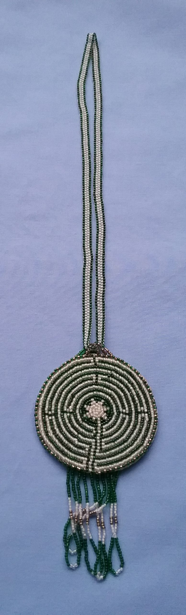 Labyrinth Necklace: Made by Sister Carol Schmit, OSF, this necklace features a beaded medallion with the eleven-circuit design of the labyrinth at Chartres Cathedral in France. The green color is meant to remind people of the healing power of walking the earth. On loan from the artist.