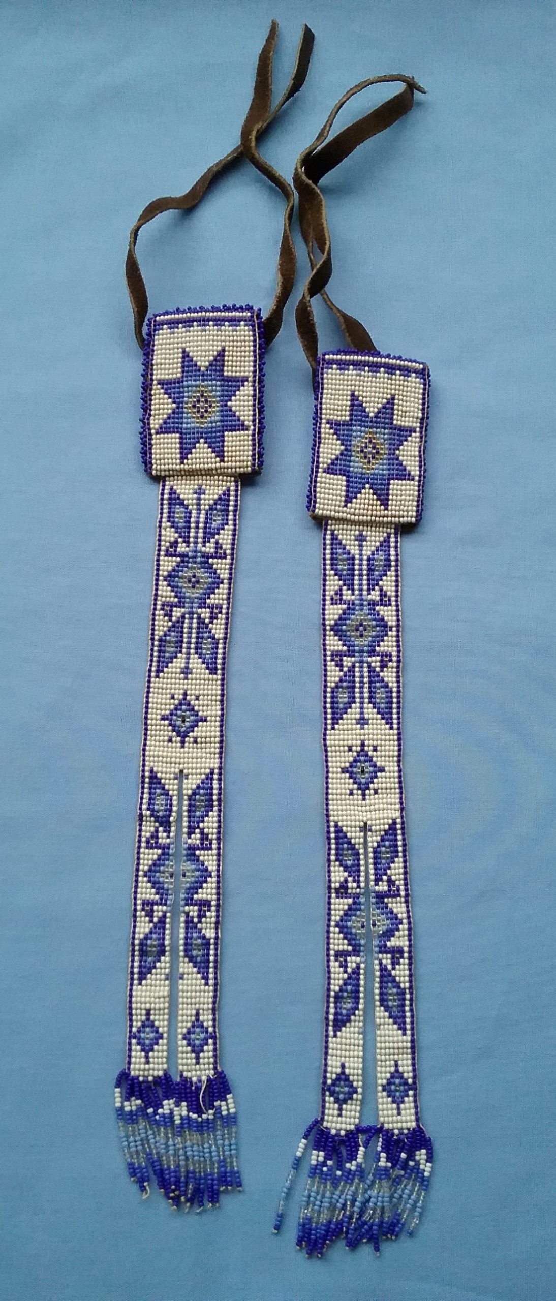 Braid Ties: These beaded blue and white braid ties were purchased in the Colorado/New Mexico area by Camille Warzecha of Little Falls, MN, for her daughter Sheryl when she was a child. They are meant to be worn tied around braided hair. On loan from Camille Warzecha.