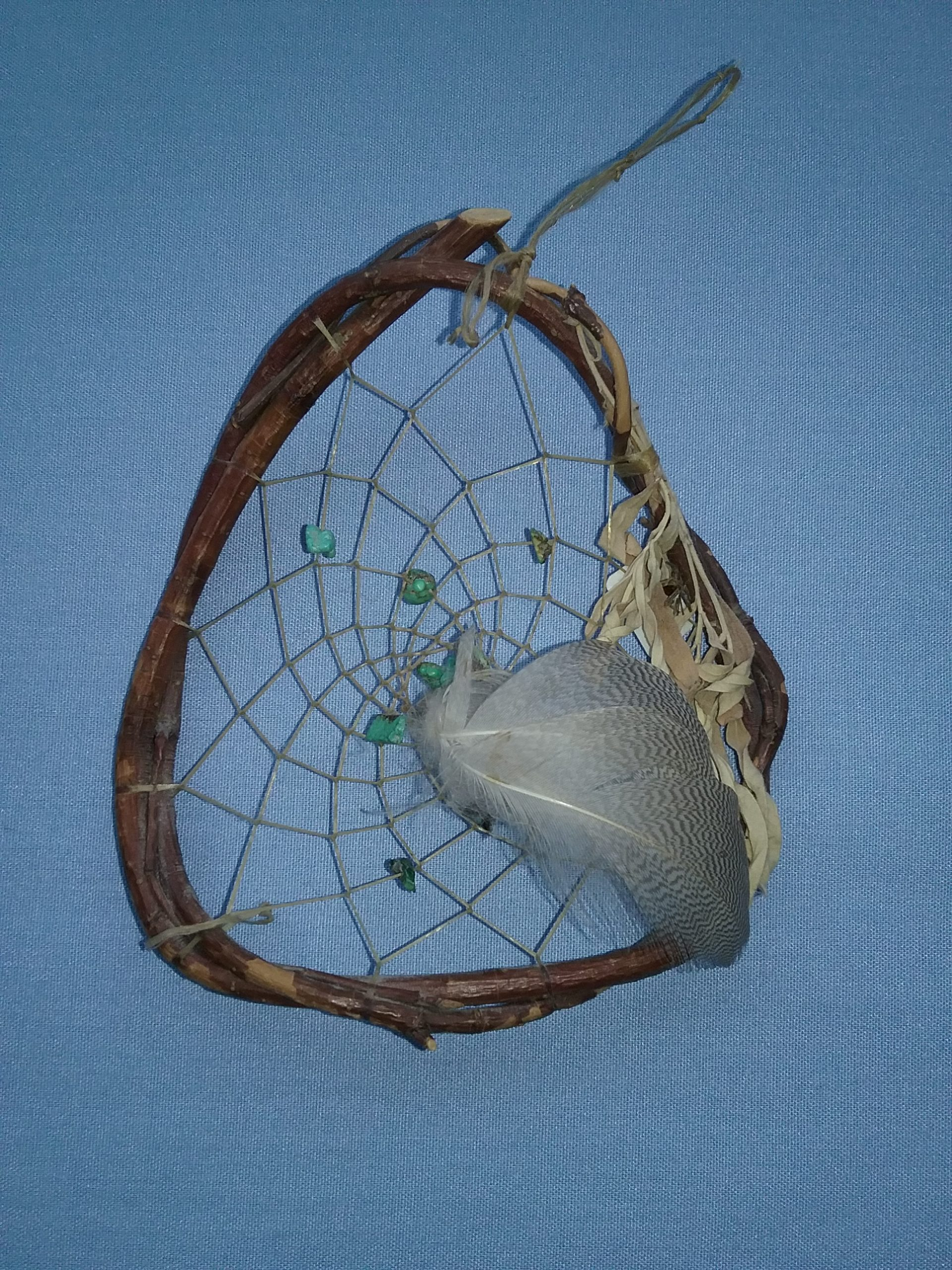 """Ojibwe dreamcatcher made by Lindalee Retka. Note the turquoise beads in the """"web"""" of the dreamcatcher. On loan from Jan Warner."""