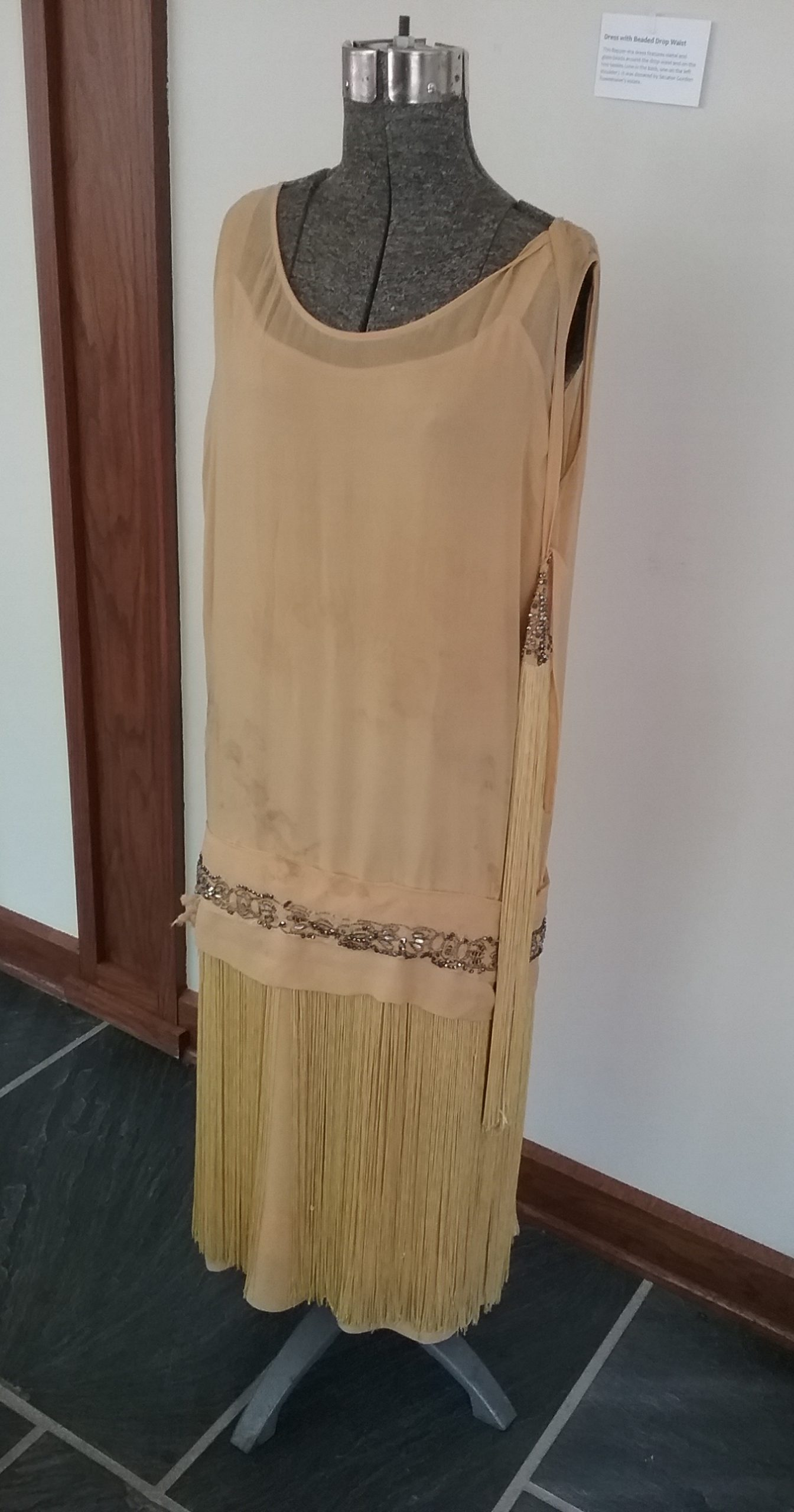 Yellow Dress with Beaded Drop Waist: This flapper-era dress features metal and glass beads around the drop waist and on the two tassels (one in the back, one on the left shoulder). It was donated by Senator Gordon Rosenmeier's estate. MCHS collections, #1994.45.51.