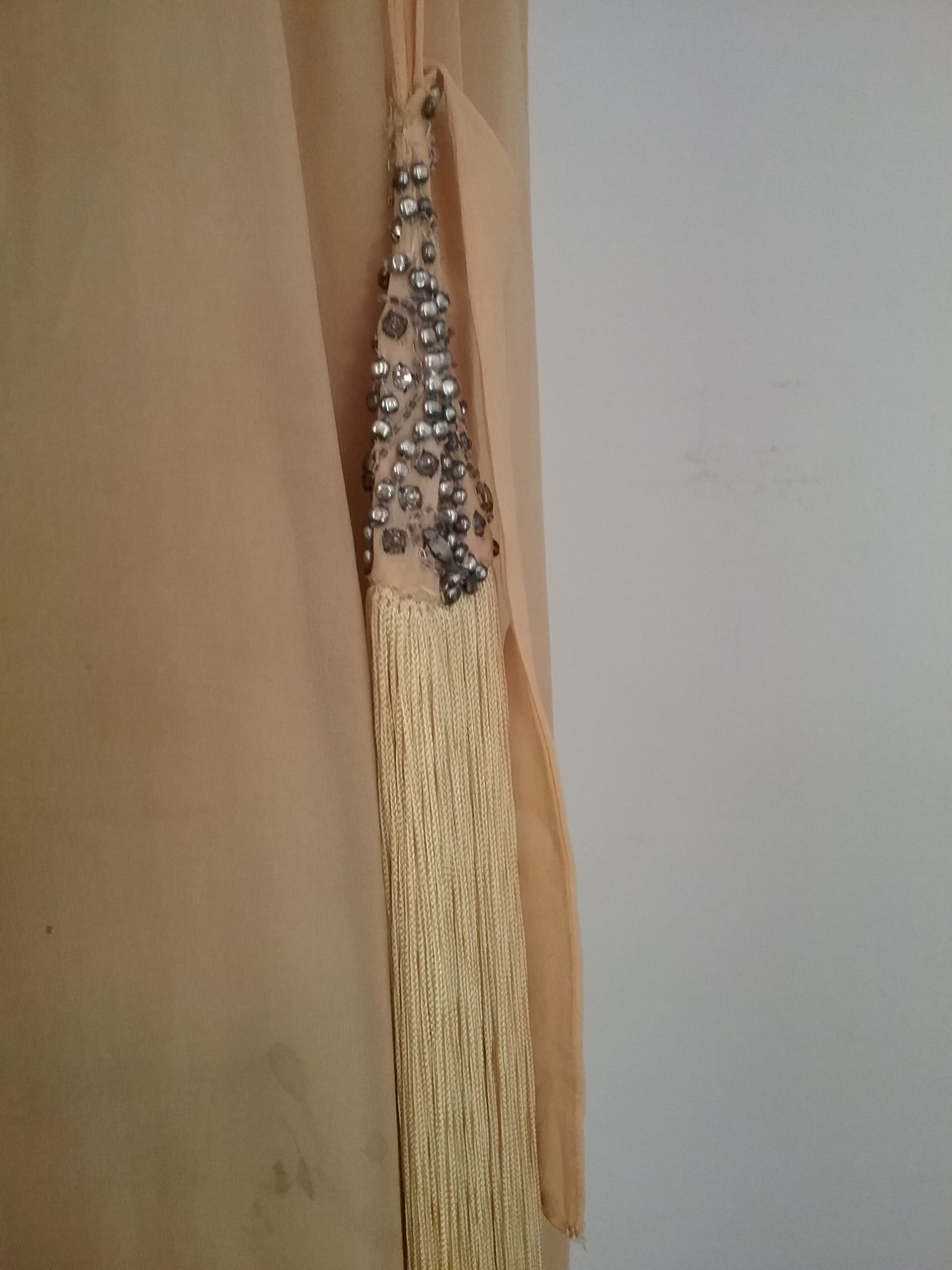 Closeup of tassel on yellow flapper-era dress with beaded drop waist. MCHS collections, #1994.45.51.