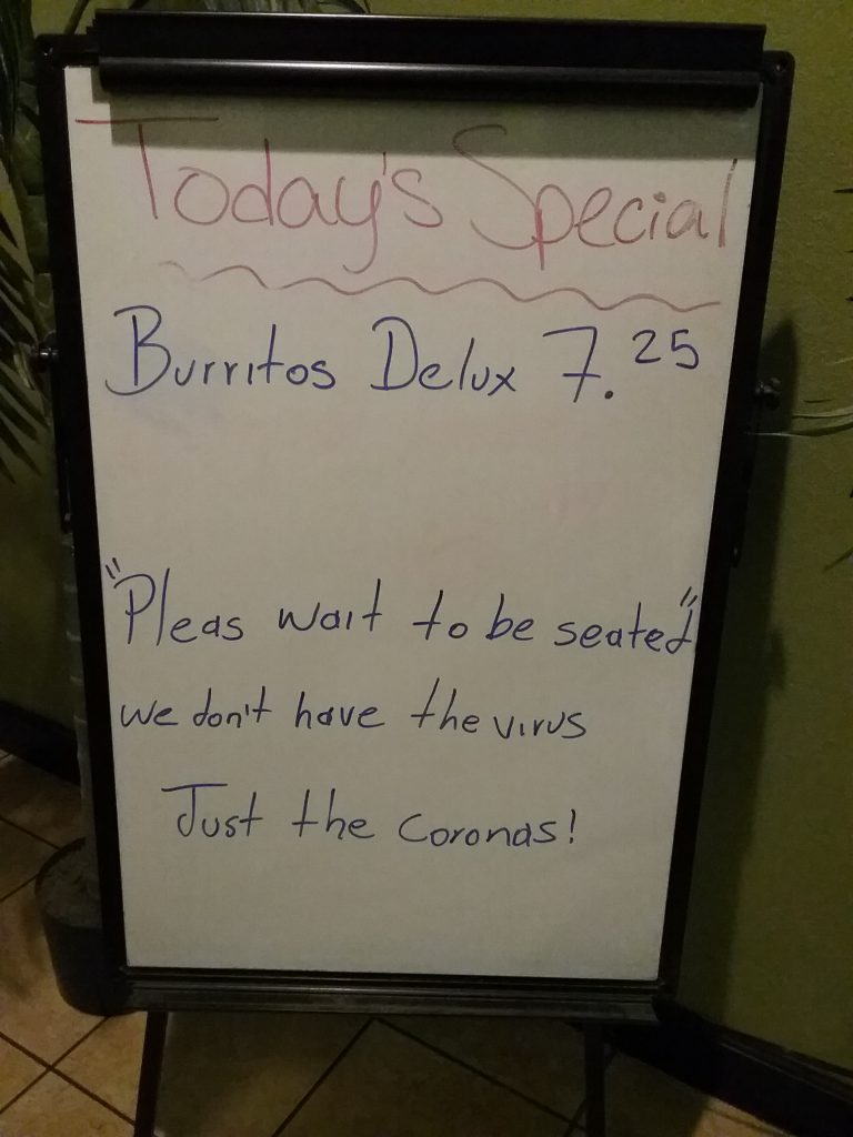 "White board sign at Little Fiesta restaurant in Little Falls, MN. It reads: ""Today's Special: Burritos Delux 7.25 - Pleas sait to be seated - we don't have the virus, Just the Coronas!"" March 5, 2020"