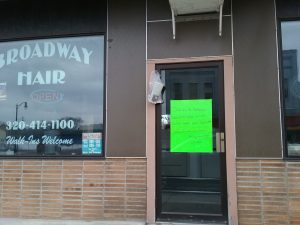 Bright green handwritten sign announcing the closure of two hair salons on East Broadway in Little Falls, MN, due to the COVID-19 pandemic, March 22, 2020.