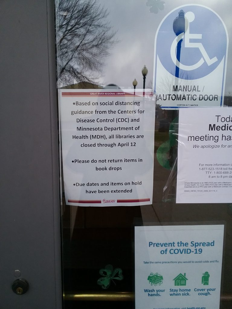 Signs on the door of the Carnegie Library in Little Falls, MN. One announces the closure of the library, including the notice to not return books. Another provides guidance to prevent the spread of COVID-19. April 15, 2020.
