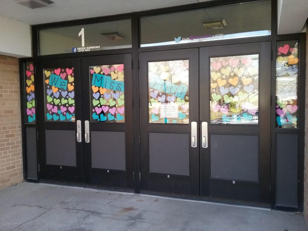 "Colorful paper hearts along with signs that say ""We Miss You!"" in the front door windows of Lincoln Elementary School, Little Falls, MN, April 15, 2020."