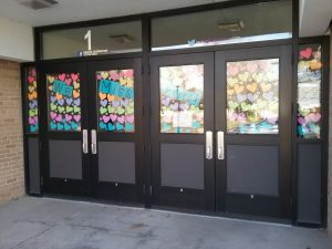 """Colorful paper hearts along with signs that say """"We Miss You!"""" in the front door windows of Lincoln Elementary School, Little Falls, MN, April 15, 2020."""