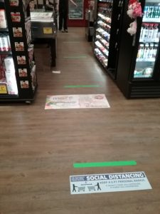 Green tape marks placed 6 feet apart in the checkout lane at Coborn's grocery store, Little Falls, MN. There is also a social distancing sign on the floor by one of the tape marks. April 15, 2020.