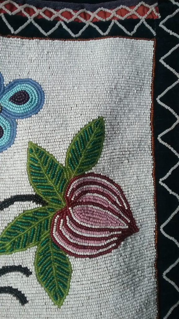 Detail of flower bud on pouch of Ojibwe gashkibidaagan owned by Ethel Gourd Hall. MCHS collections, #1954.8.1.