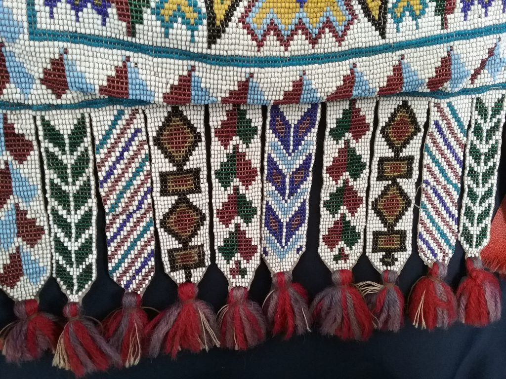 Detail of beaded fringe with tassels on Ojibwe gashkibidaagan owned by Nathan Richardson. MCHS collections, #1940.42.1.