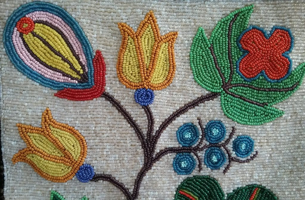 Closeup of beadwork on pouch of small Ojibwe gashkibidaagan. These beaded plants were inspired by real-world plants and can be identified by Ojibwe people who study and work with these plants. MCHS collections, #1996.36.3.