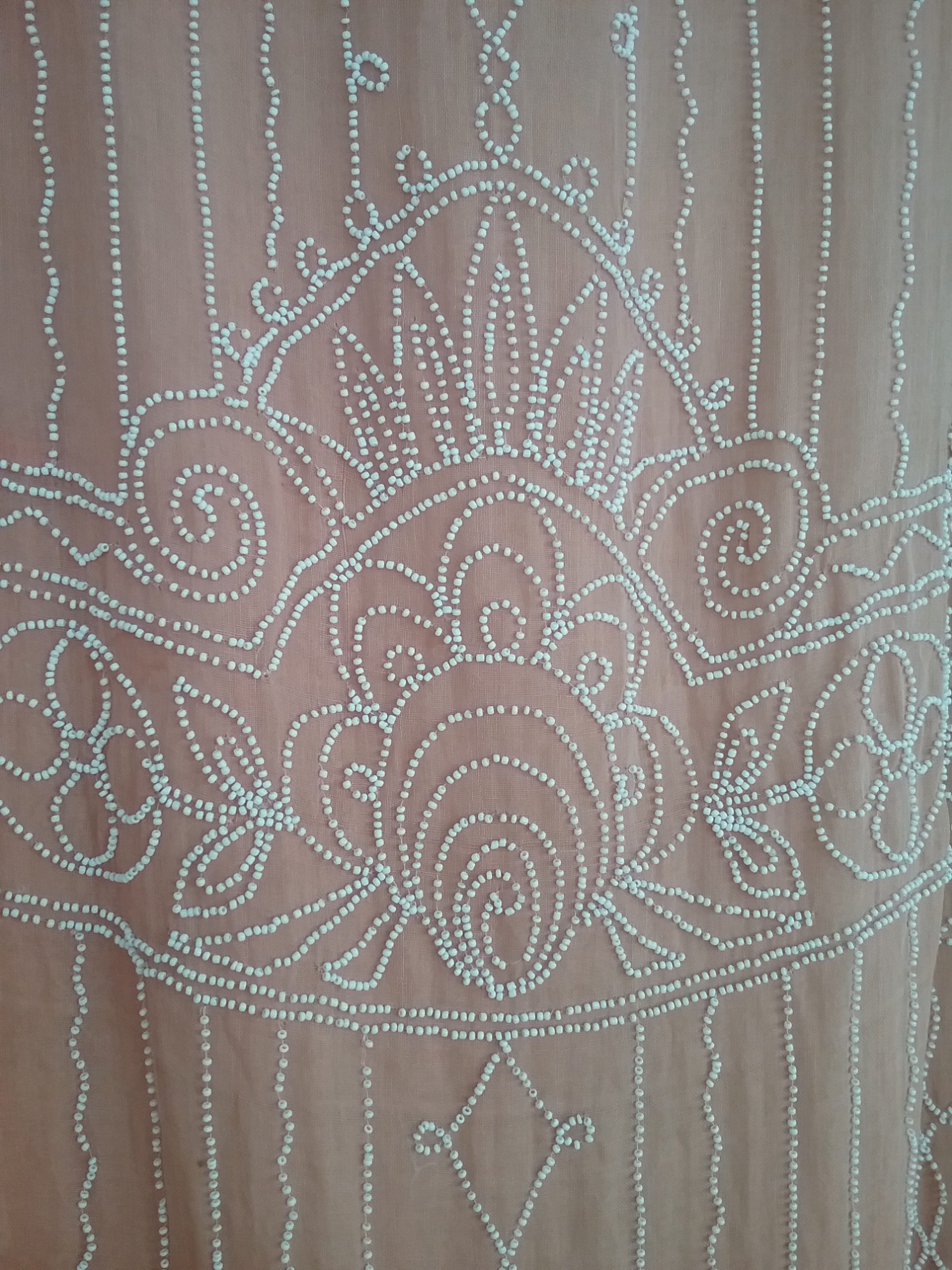 Closeup of beadwork on peach gauze beaded dress. MCHS collections, #1971.10.42.