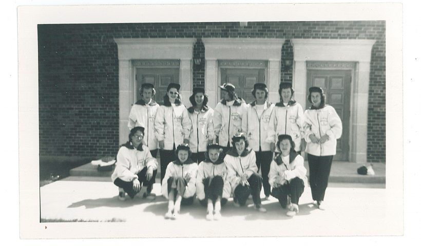 Ski Patrol, Winter Wonderland, Little Falls, MN, 1950. MCHS collections #1992.40.4. - Twelve women dressed in matching winter outfits, white coats with black front zippers and collars and black pants.