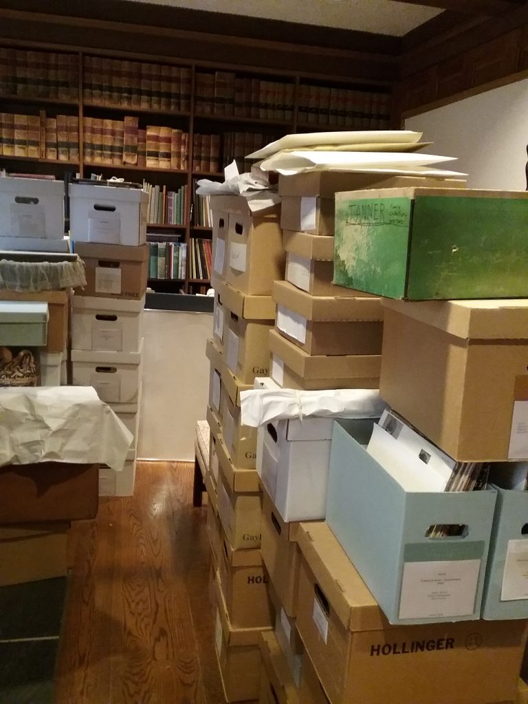 Boxes of collections items temporarily stacked in the R.D. Musser Library at The Charles A. Weyerhaeuser Memorial Museum, Little Falls, MN, in advance of the replacement of the HVAC system. Photo taken October 2, 2021.