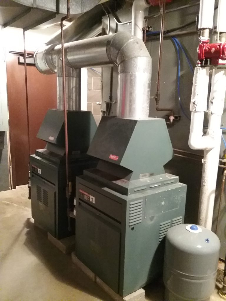 Gas boilers in front of air handler in the furnace room at The Charles A. Weyerhaeuser Memorial Museum, Little Falls, MN. This system was originally installed when the museum was built in 1974/75, with the gas boilers being an upgrade in the 1990s. Photo taken October 2, 2021.